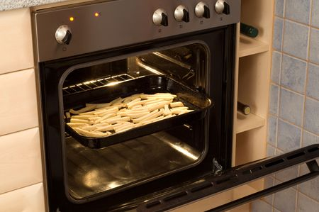 Open built-in electric oven with French fries inside