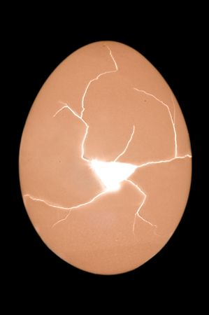 Cracking egg with hole and radiant light from inside on black Stock Photo