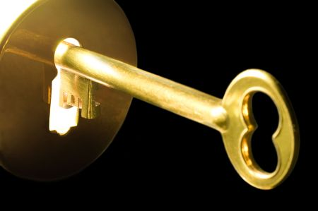 A golden key in a keyhole on black background