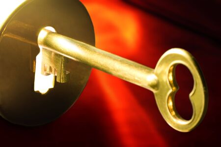 A golden key in a keyhole illuminated by a mysterious light