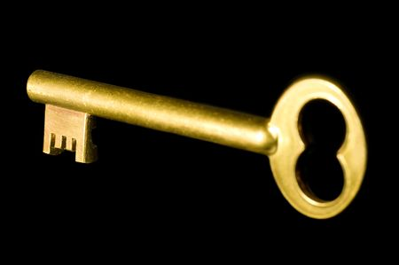 A shiny old-style golden key isolated on black background Stock Photo