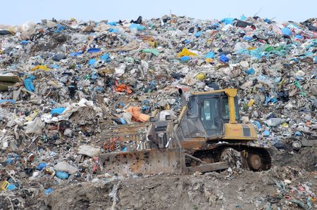 Bulldozer on heap of rubbish and trash on a dump Stock Photo
