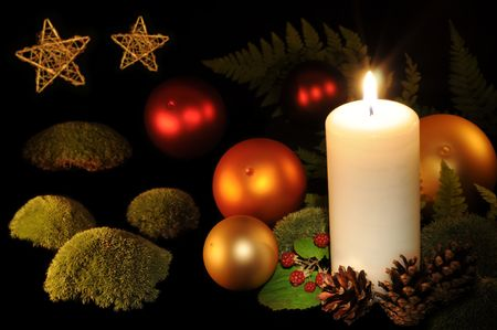 Christmas balls, burning white candle, berries, moss and fern photo