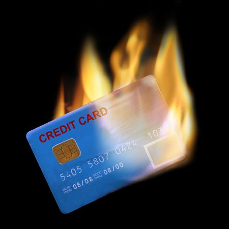 Bank credit card in flames on black background