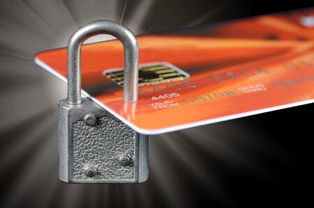 A bank credit card locked by a padlock with flare Stock Photo
