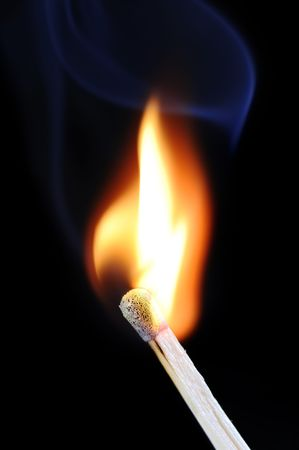 Burning fire of a match on black background with blue smoke photo