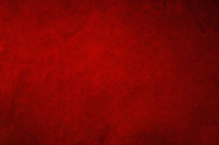 Dark red background fabric with soft folds and smudges in candlelight.