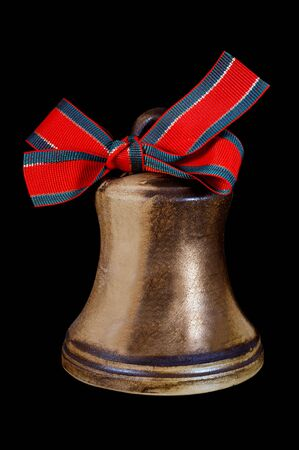 Brown ceramic Christmas bell with red ribbon on black photo