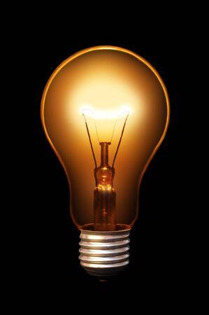 Classical old style bulb shining on black background. Reklamní fotografie