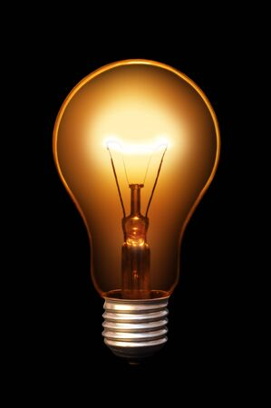Classical old style bulb shining on black background. Stock Photo