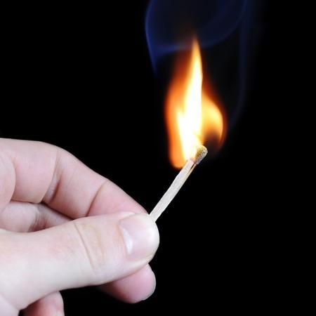 cerillos: Lado la celebraci�n de una cerilla encendida sobre fondo negro Foto de archivo