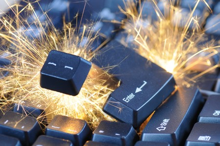 Black exploding computer keyboard with electric sparks. Stock Photo