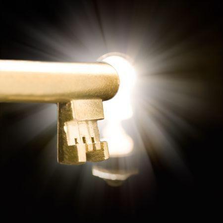 Einem goldenen Schlüssel in ein Schlüsselloch mit einem geheimnisvollen Licht beleuchtet