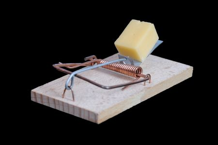 Mousetrap with a piece of cheese on black background. Stock Photo