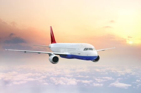 Transport airplane flying in the sky at sunset Stock Photo