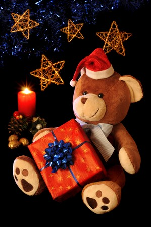 Christmas teddy bear with gift and holiday decoration. photo