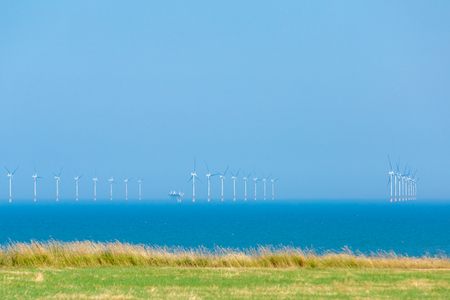 Offshore wind farm against a hazy blue sky and sea with wild golden grass and a green field in the foreground