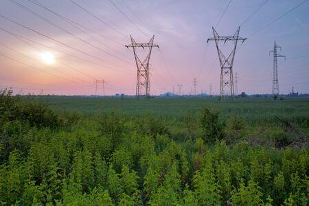 balkan peninsula: Sunset over Highvoltage power lines  in the land around Plovdiv Bulgaria Stock Photo