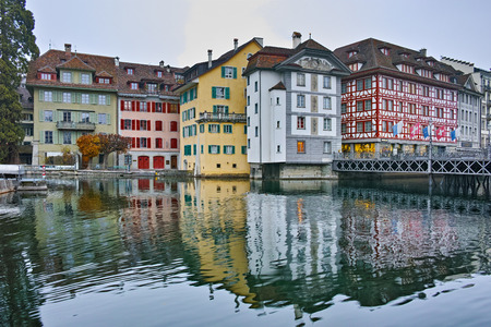 swiss culture: City of Luzern and reflection of old town in The Reuss River, Switzerland Editorial