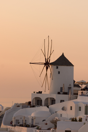 thira: Sunset over white windmills in  town of Oia and panorama to Santorini island, Thira, Cyclades, Greece