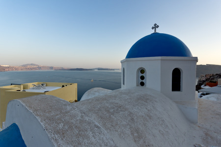 thira: Church with blue roof in town of Oia and panorama to Santorini island, Thira, Cyclades, Greece Stock Photo