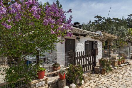 paisaje mediterraneo: Viejas casas de piedra y flores de color violeta en el pueblo de Aliki, la isla de Tasos, Macedonia oriental y Tracia, Grecia