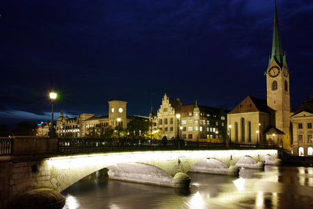 grossmunster cathedral: Night photo of Fraumunster Church and bridge over Limmat River, city of Zurich, Switzerland Editorial