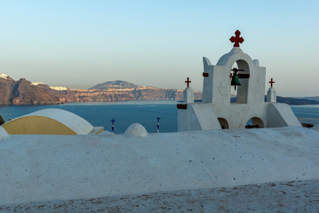 Church with blue roof in town of Oia and panorama to Santorini island, Thira, Cyclades, Greece Stock Photo
