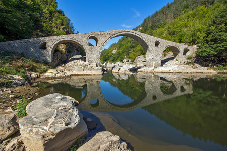 Amazing Reflection of Devils Bridge in Arda river, Kardzhali Region, Bulgaria Stock Photo