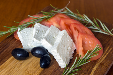 feta cheese: Fresh salad with tomatoes, feta cheese and olives on wooden background