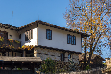 Panorama with autumn tree and old house in village of Bozhentsi, Gabrovo region, Bulgaria