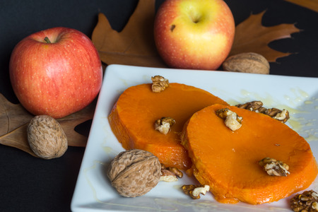 Roasted, baked pumpkin with addition of Honey and walnuts and autumn leafs Stock Photo
