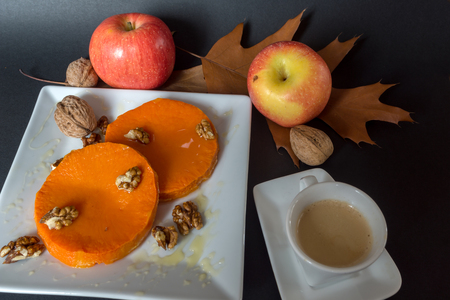 Roasted, baked pumpkin with addition of Honey and walnuts, autumn leafs and  cup of coffee