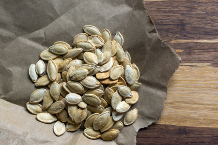 pumpkin seeds: Grilled Pumpkin seeds with sea salt and spices on the wooden background
