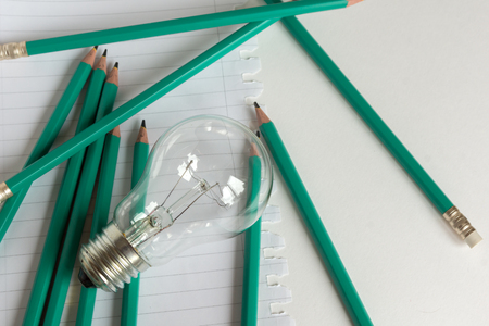 composition notebook: Composition with Light bulb with notebook and pencils on white background Stock Photo