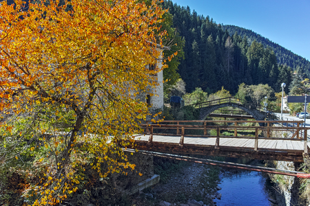 19th century Church of the Assumption, river and Autumn tree in town of Shiroka Laka, Smolyan Region, Bulgaria Stock Photo