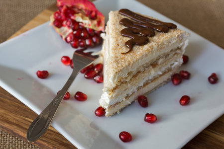 Portion homemade cream cake with pomegranate seeds and chocolate spread. Macro view.