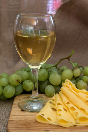 tabla de quesos: still life with glass of white wine, cheese and grapes on wooden background