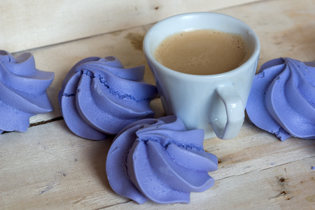kiss biscuits: French blue meringue cookies and cup of coffee on white wooden background Stock Photo