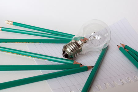composition notebook: Business Composition with Light bulb with notebook and pencils on white background