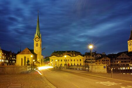 Night photo of Fraumunster Church and bridge over Limmat River, city of Zurich, Switzerland Stock Photo