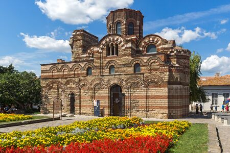 NESSEBAR, BULGARIA - AUGUST 12, 2018: Flower garden in front of Ancient Church of Christ Pantocrator in the town of Nessebar, Burgas Region, Bulgaria