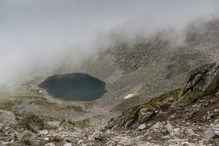 Panorama of Ledenoto (Ice) Lake and clouds over Musala Peak, Rila mountain, Bulgaria