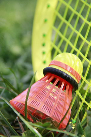 Close up badminton racket and shuttlecock laying on the green grass Stock Photo