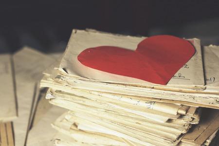 cartas antiguas: Viejas cartas con un corazón de papel Foto de archivo