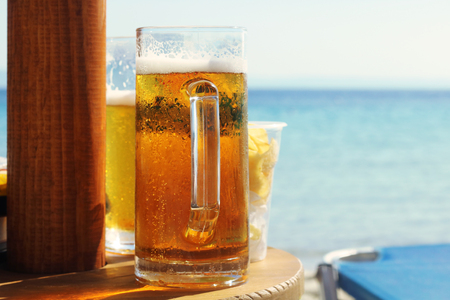 Cold beer on wood table in front the sea of Greece Stock Photo