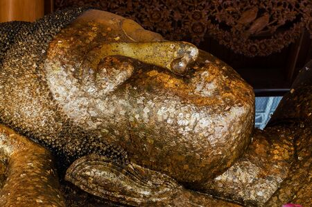 Face of Sleeping Buddha in temple of thailand. Big reclining buddha is creed buddhist. Gold leaf gilded on Buddha Stock Photo