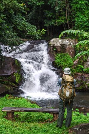 Hiking. Hikers male with a backpack and a hat looking at a waterfall in the forest, Phu Soi Dao National Park, Thailand. Фото со стока