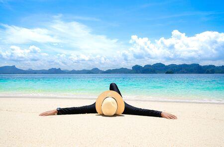 Woman relaxing on beach, lying down tropical beach, ocean view, Poda Island, Krabi, Thailand.