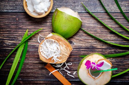 Fresh coconut, ready to drink with coconut flesh in coconut shell and bowl on beautiful decorative wooden floor